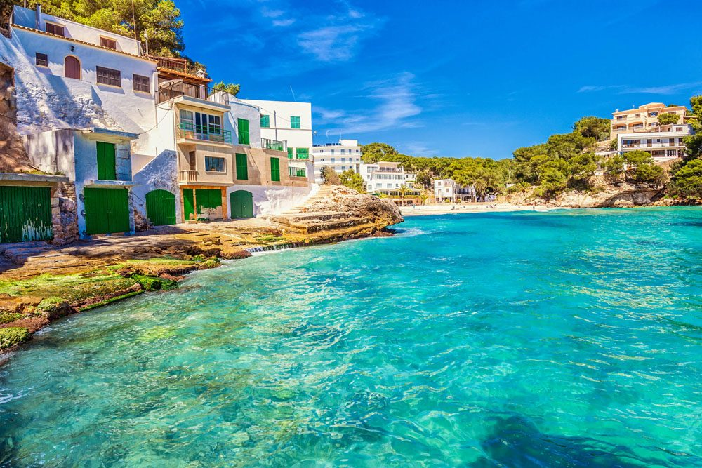 Beautiful traditional boathouses, apartments and beach at Playa Santanyi, located in the south east of Mallorca.