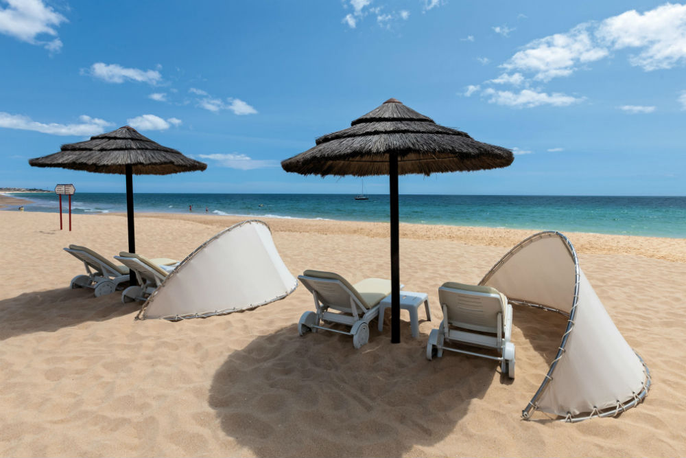 beach chairs and palapa on the sandy shore of the Algarve beach in Portugal