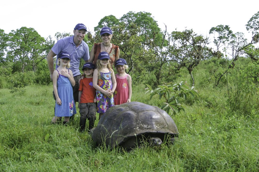 family with giant tortoise on galapagos island