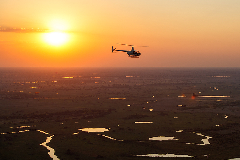 Botswana helicopter at sunset over the savannah Desert & Delta Safari