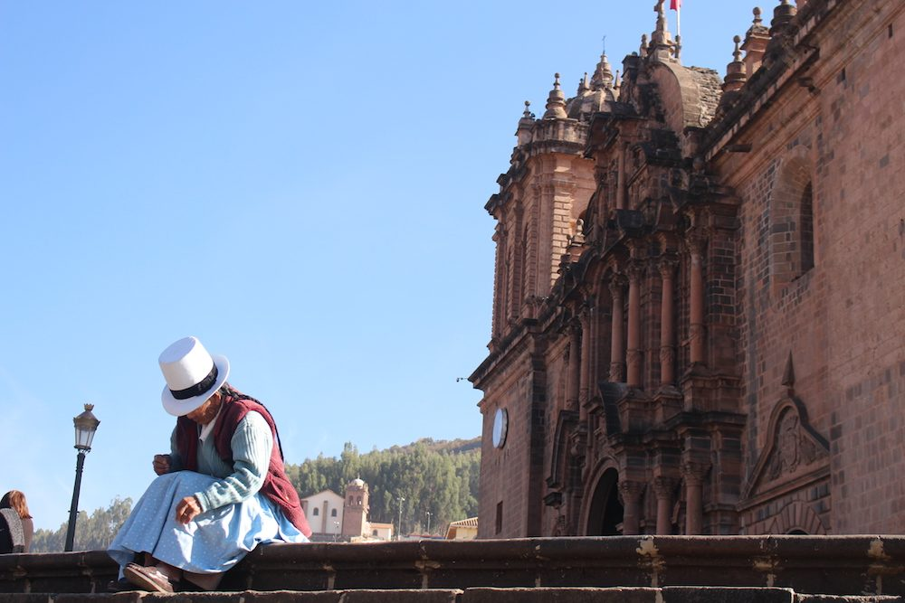 Woman in Main Square of Cusco Peru with old building behind her. Photo from Aracari travel