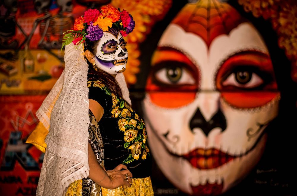 Day of the Dead with painted skull face and doll in Oaxaca Mexico