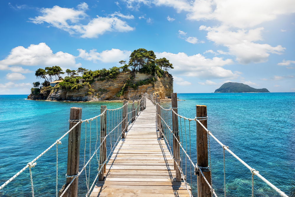 pier walking bridge over turquoise water going to a small island with trees Agios Sostis Greece
