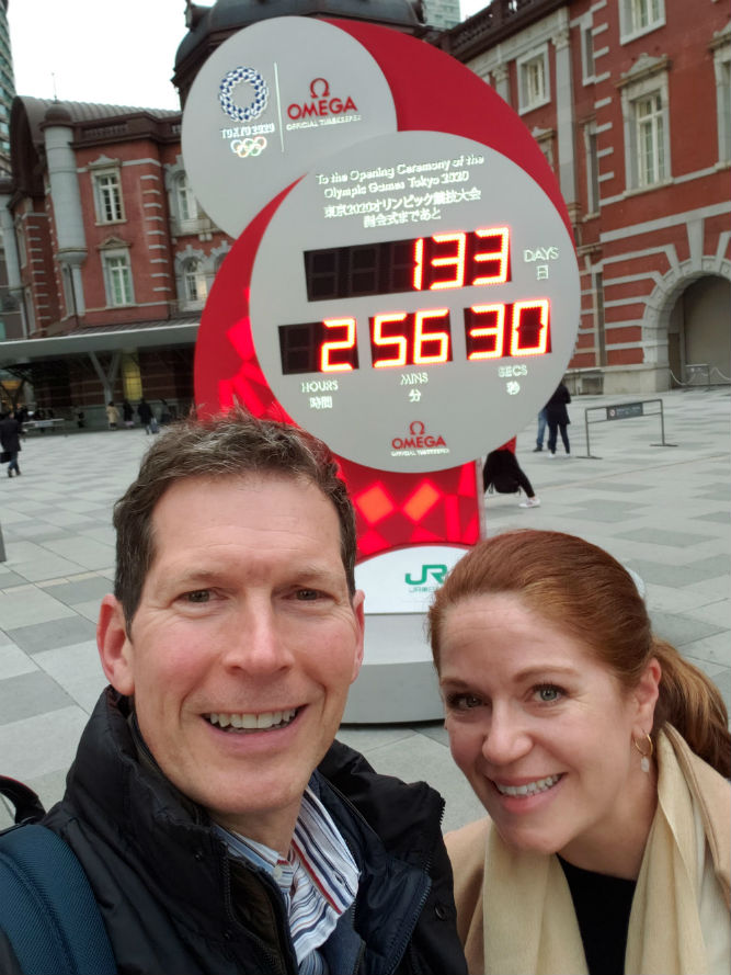 tourist couple selfie in front of countdown clock to Tokyo Olympics in Japan