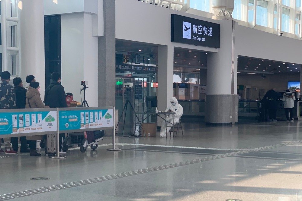 Chengdu Airport on January 30 with masked, fully suited person waiting to do screenings of travelers in line