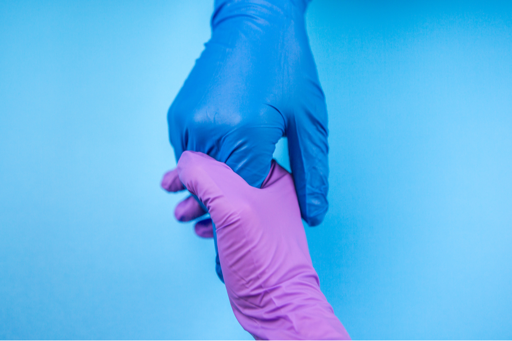 A doctor's hand saving the patient holding his hand in a glove on blue background. Concept of salvation, donorship, helping hand, coronavirus, COVID 19
