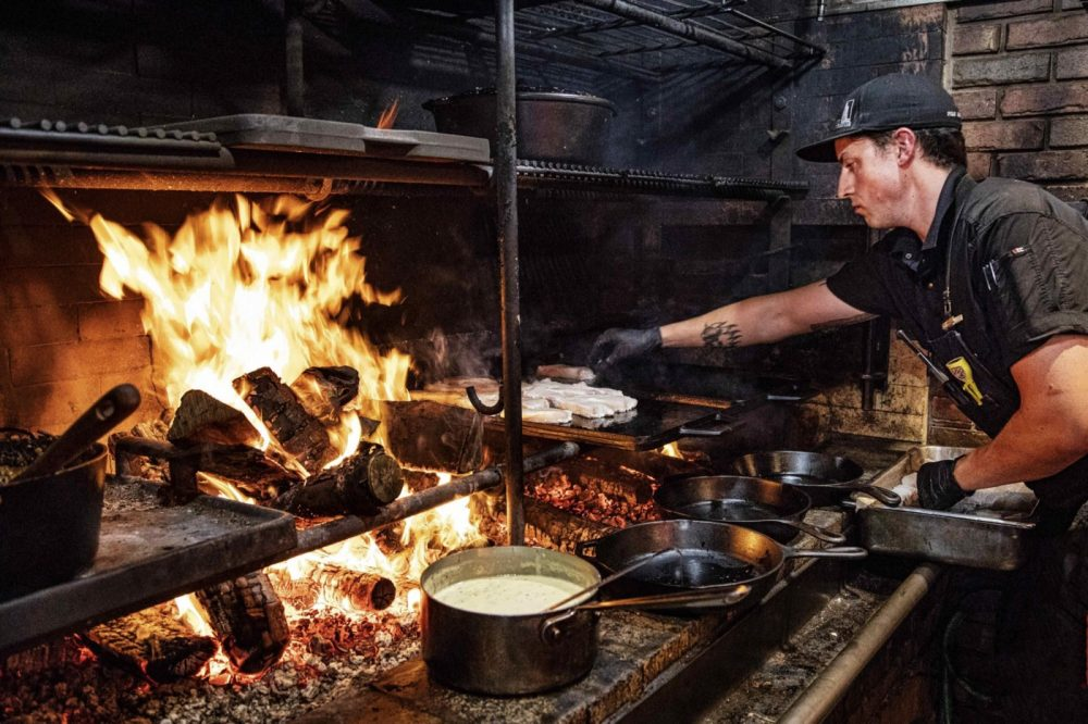 chef cooking over fire at Inn at Bay Fortune Prince Edward Island Canada