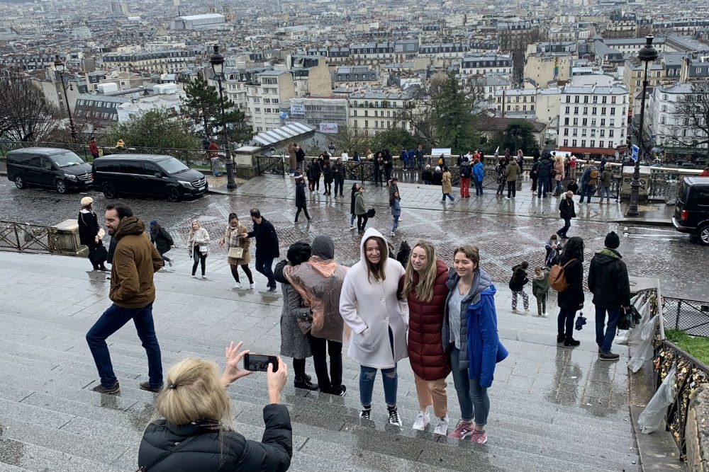 family stands to take a photo in the rain in Paris France