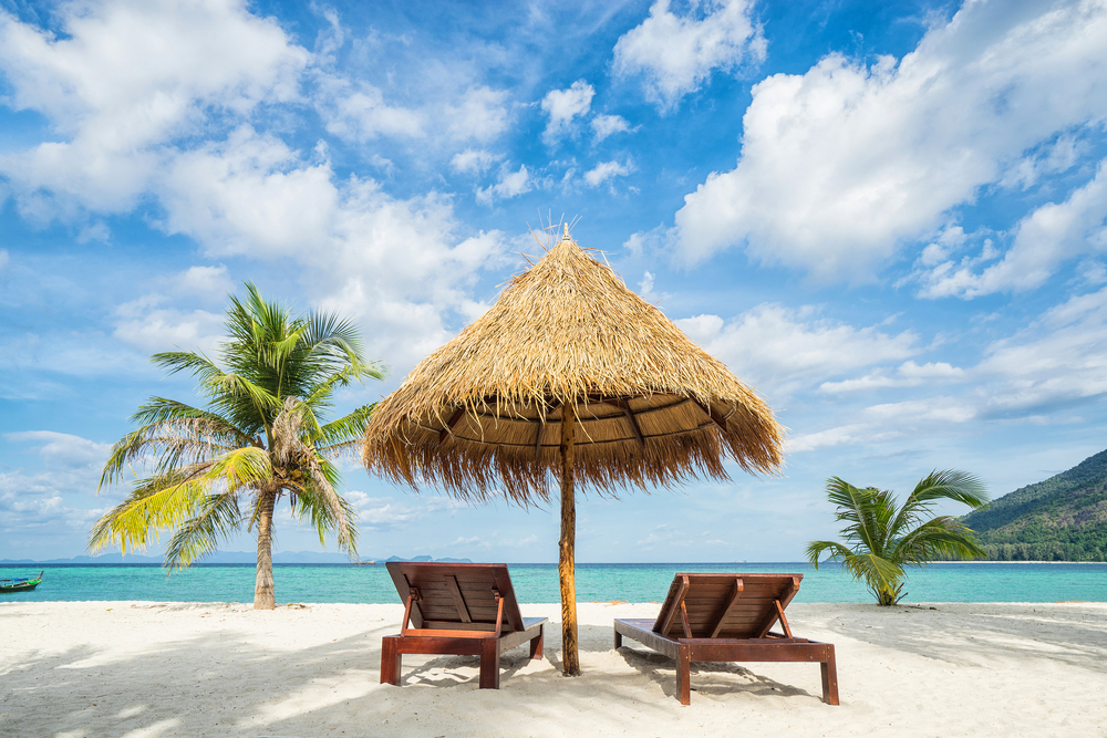 palapa with two beach chairs on a beach with turquoise ocean and palm trees
