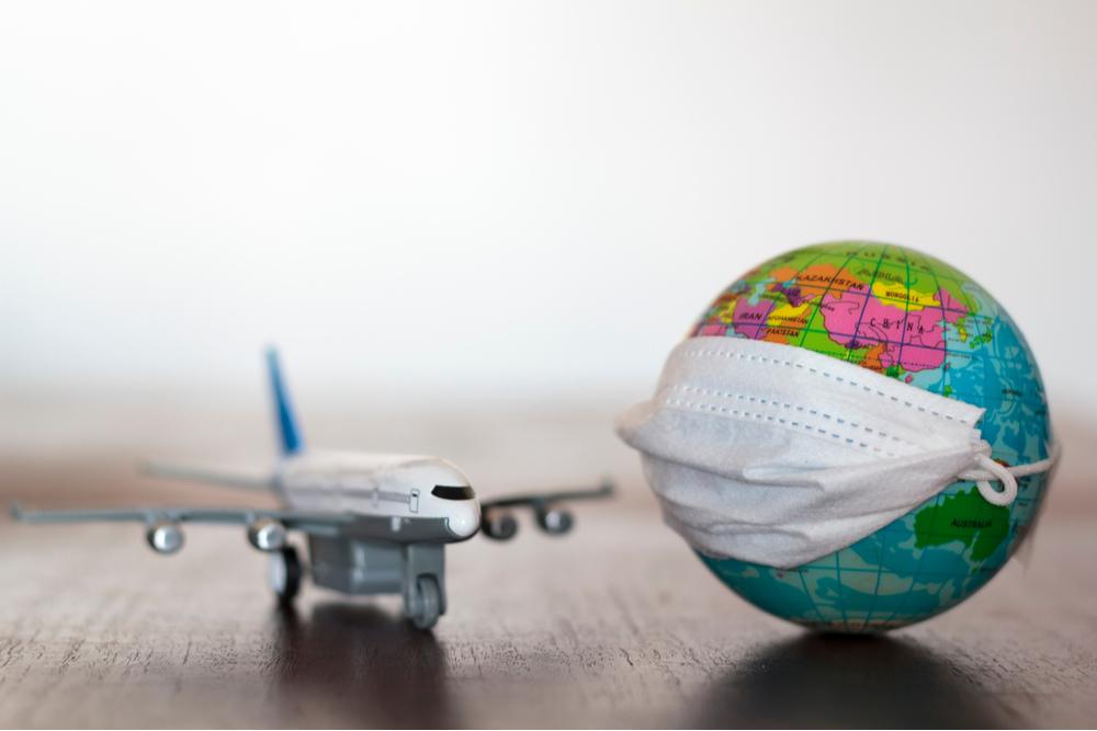 World globe with medical mask and airplane. Pandemic concept, Virus, Coronavirus, Covid-19, international emergency, global quarantine