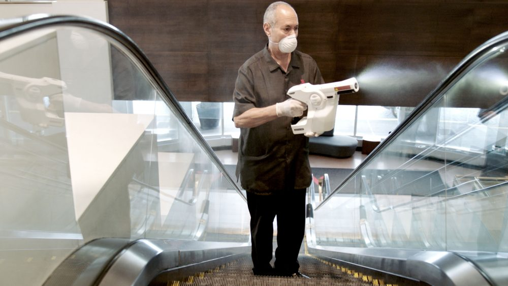worker using electrostatic sprayer to clean hotel escalator for coronavirus covid safety