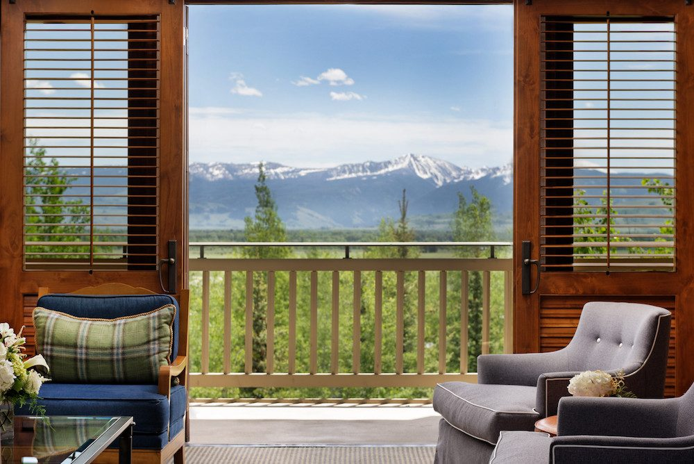Four Seasons Jackson Hole hotel room with balcony doors open overlooking mountains