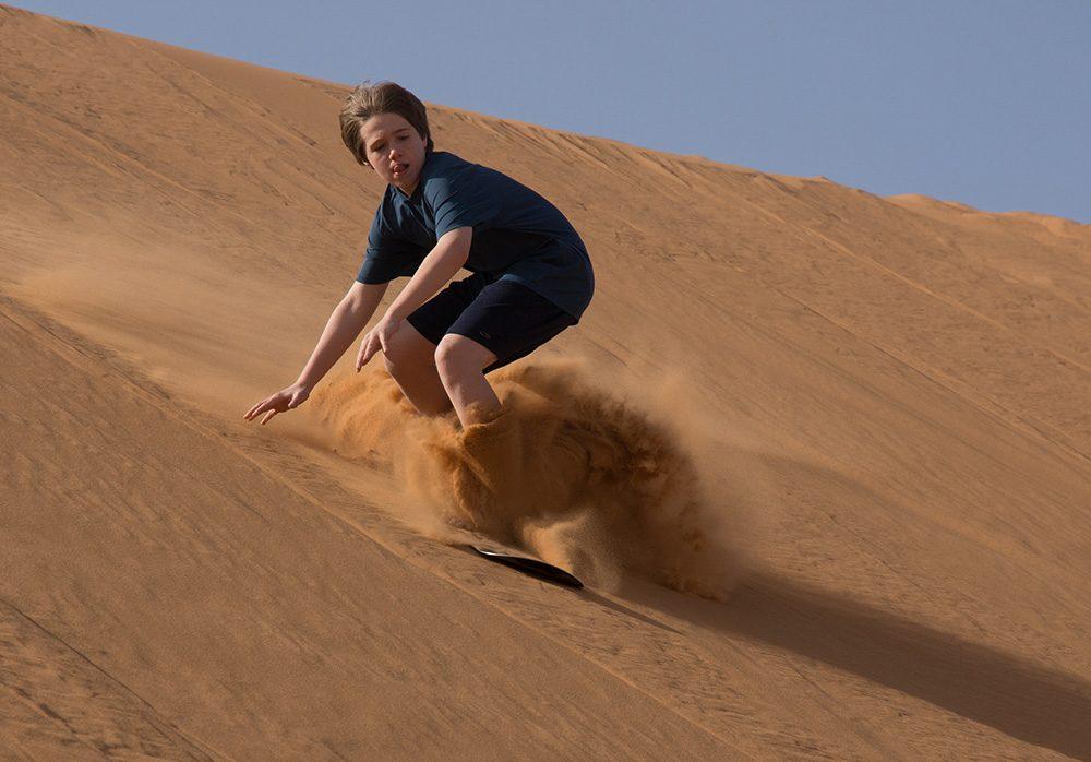teenage boy Sand Boarding in the Moroccan Dunes