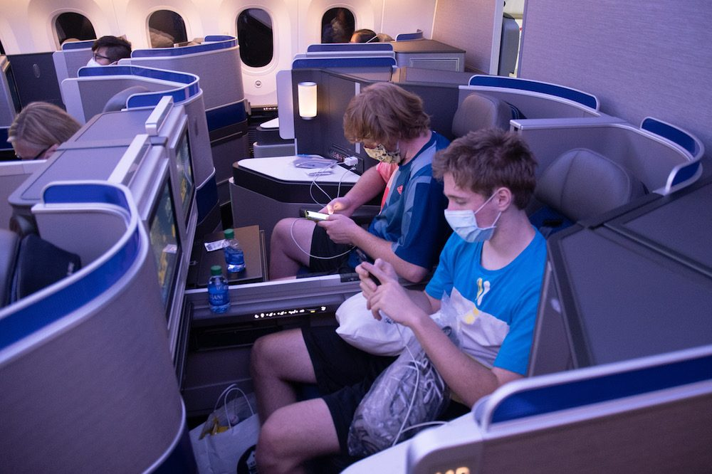Two teenage boys with masks on in business class of a United airplane during coronavirus