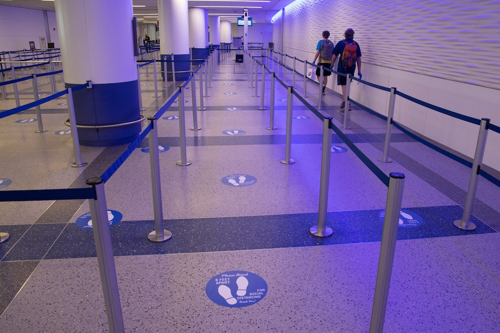 Two teenage boys walking through empty TSA airport security during coronavirus