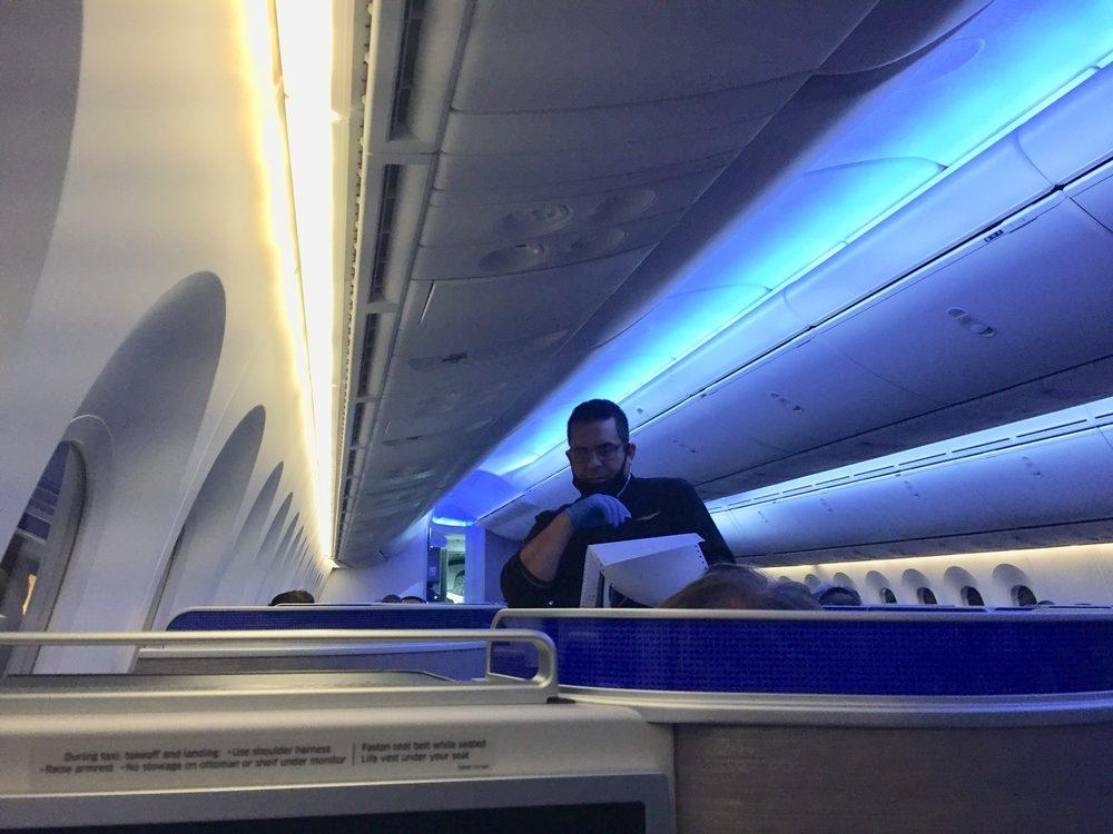 United flight crew attendant with mask around chin
