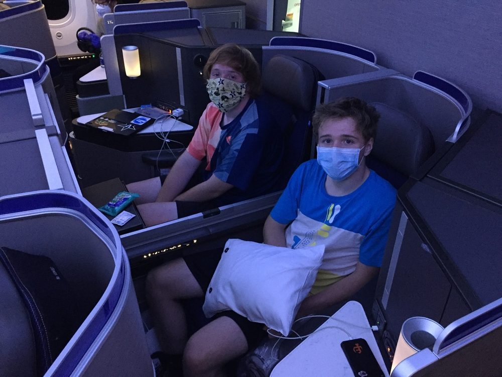 teenage boys traveling in business class United flight with masks on