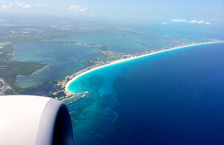view out of airplane window of Cancun Mexico with jet engine in bottom corner