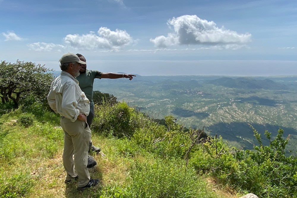man and guide looking over view in Africa