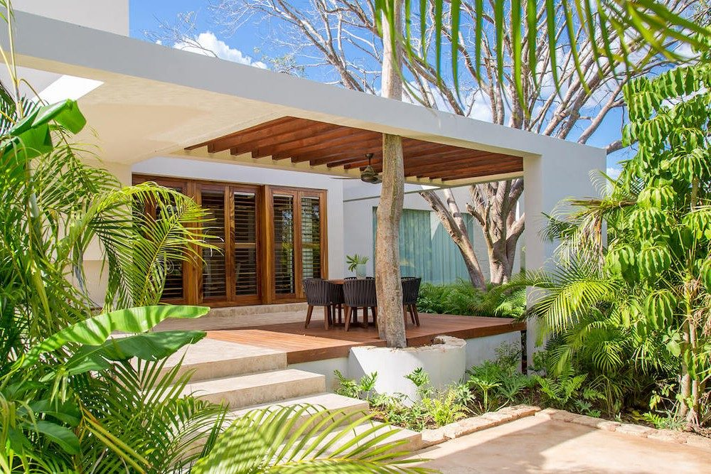 outdoor porch dining area of a vacation villa at Chable resort in Mexico with green trees around
