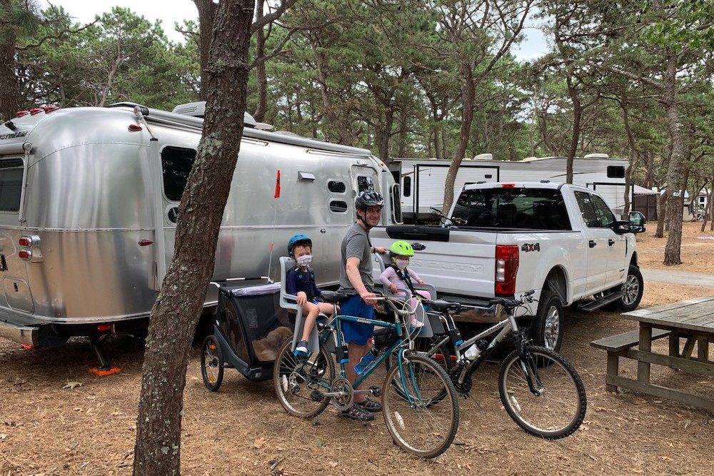 dad with kids on bikes in a RV campground
