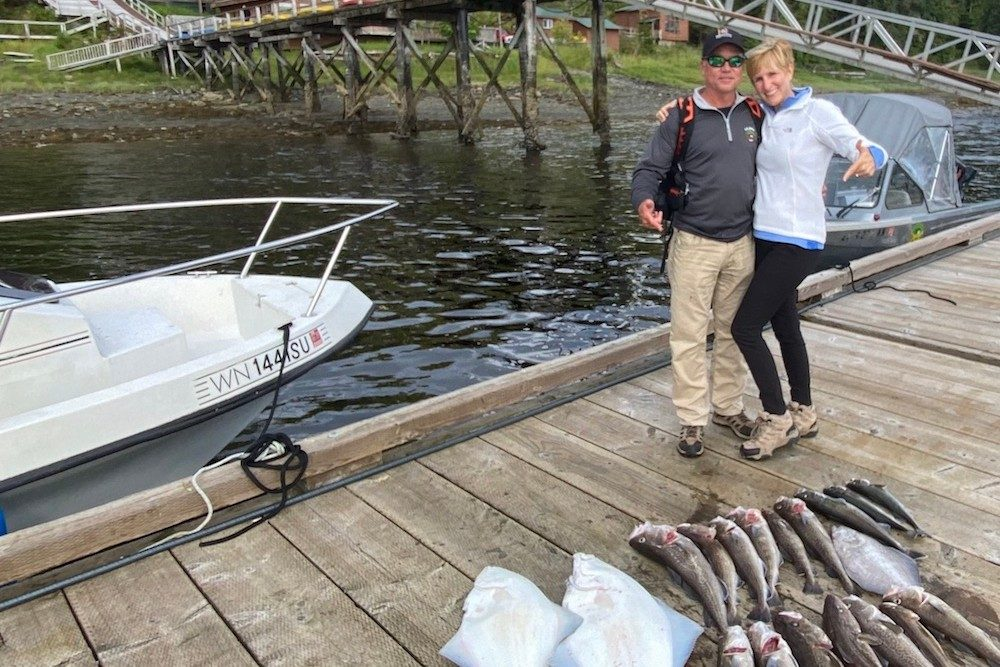 couple on boat dock in alaska posing with fish from fishing trip