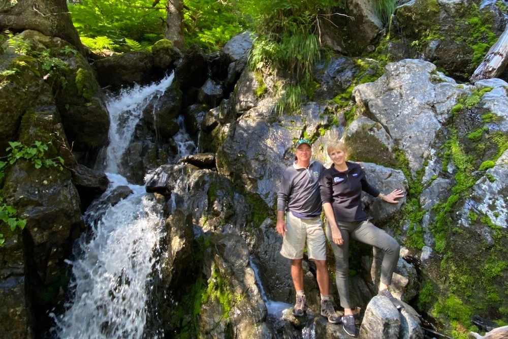 a couple poses in the woods by a waterfall in Alaska