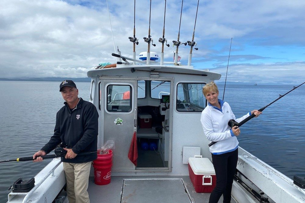 couple fishing off back of boat in Alaska