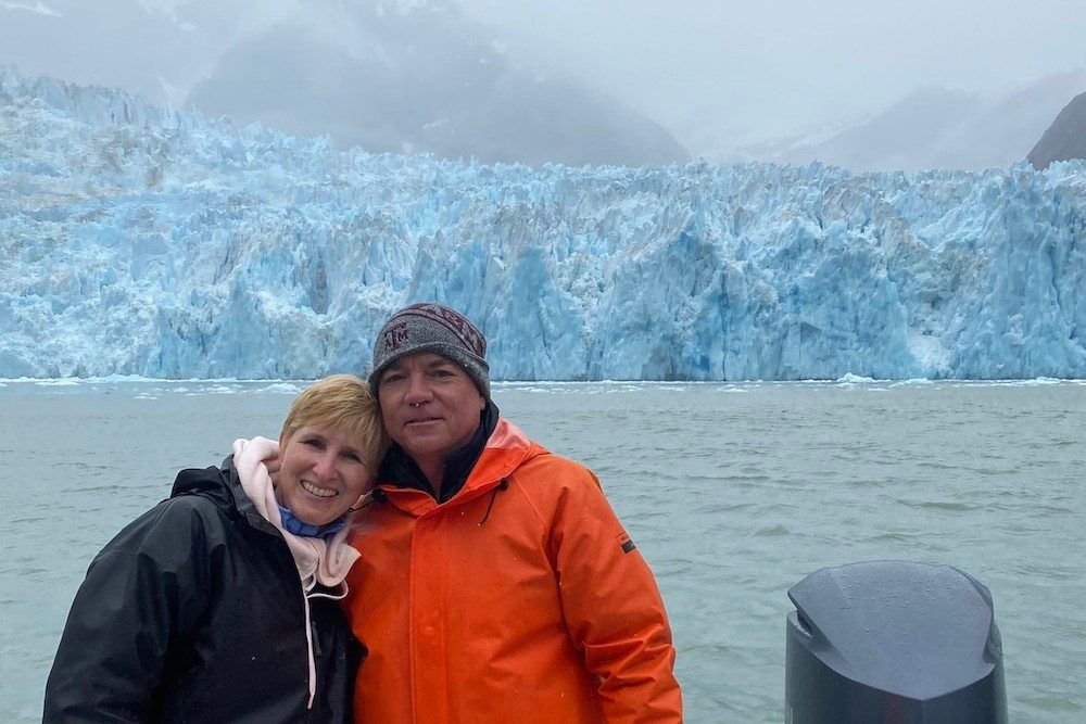 couple posing on a boat in front of a glacier in Alaska