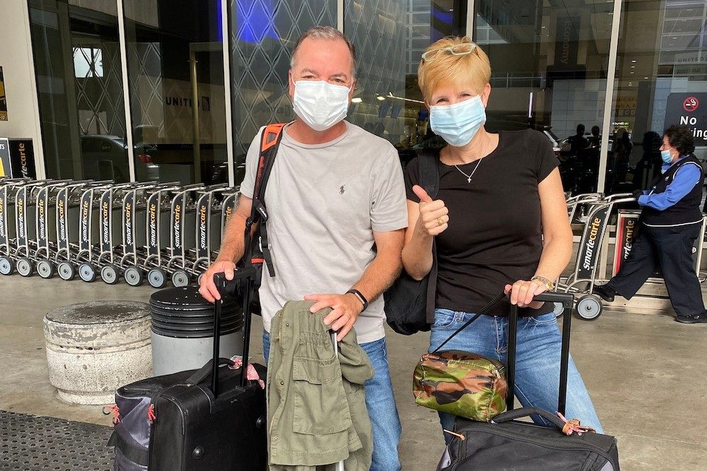 couuple in masks with luggage at airport