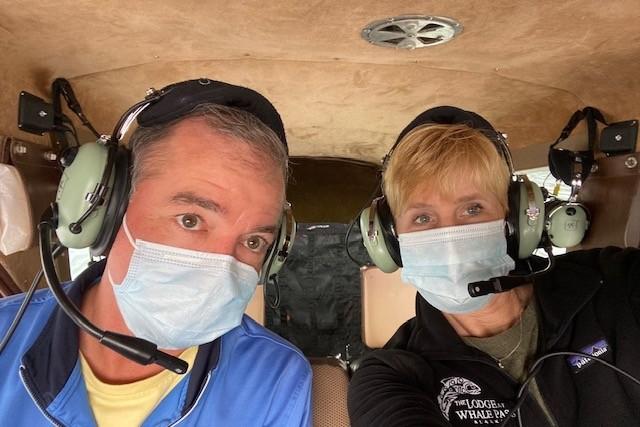 traveler couple wearing masks in a float plane in Alaska
