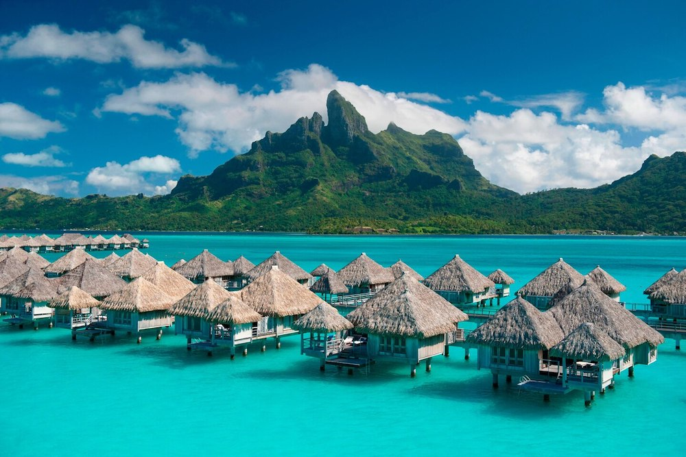 overwater bungalows at St. Regis Bora Bora with mountain in background