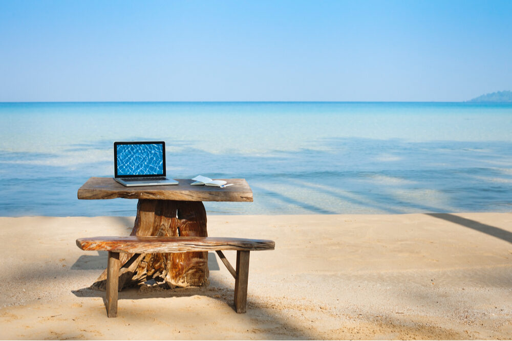 laptop computer open on picnic table on beach, work from vacation concept