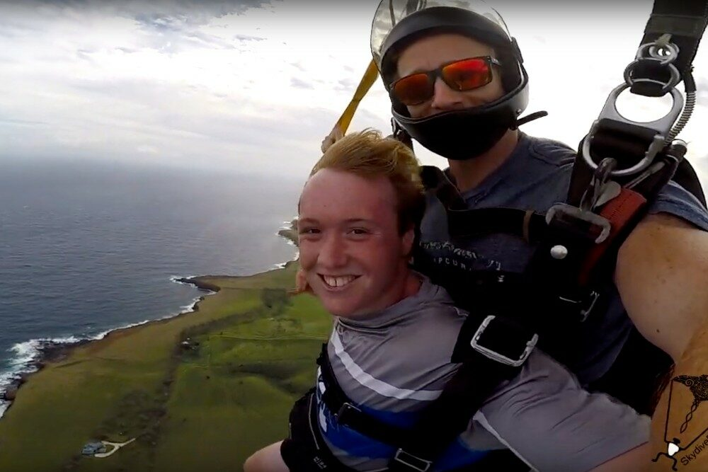 teenage boy tandem skydiving selfie over Hawaii