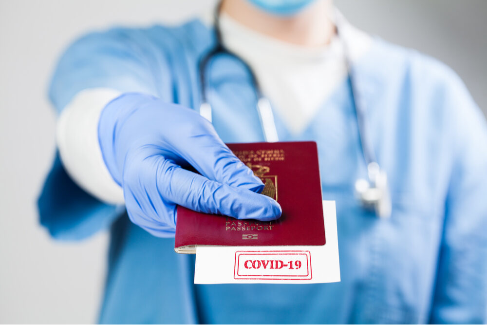 Doctor holding passport with COVID-19 sign stamped onto a white paper,immunity passport or risk-free certificate concept,recovered Coronavirus COVID19 patients being issued proof of convalescence, UK