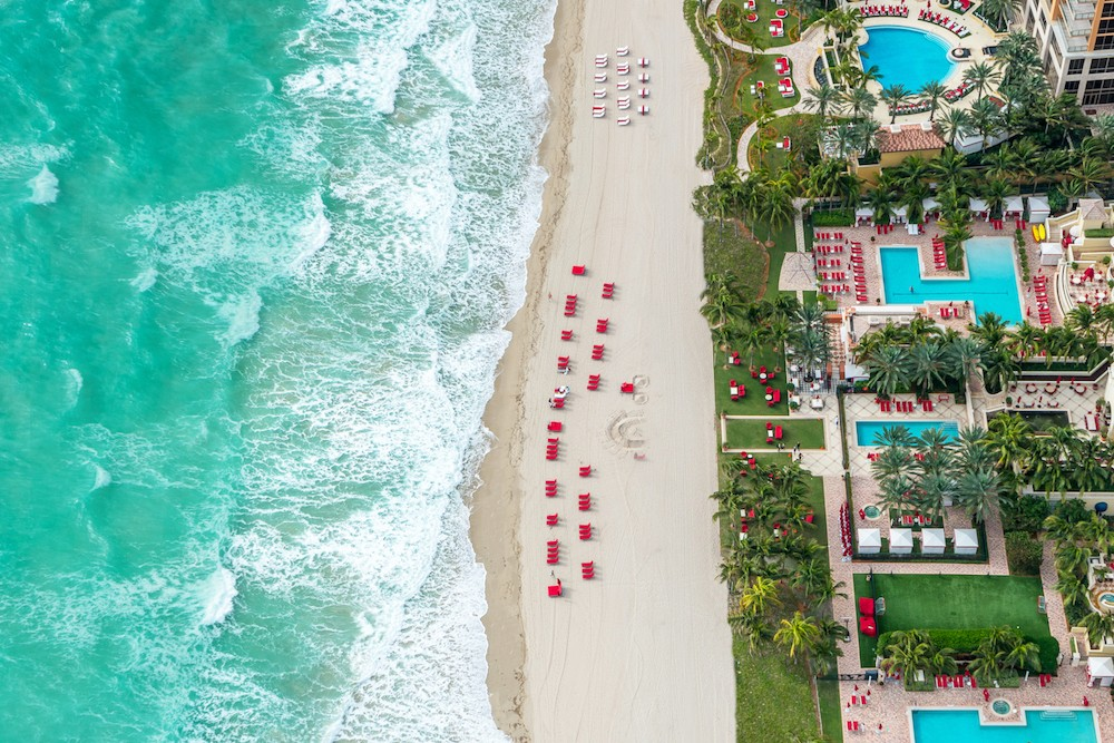 aerial photo of red chairs on beach next to ocean and resort pools at Acqualina Resort in Florida