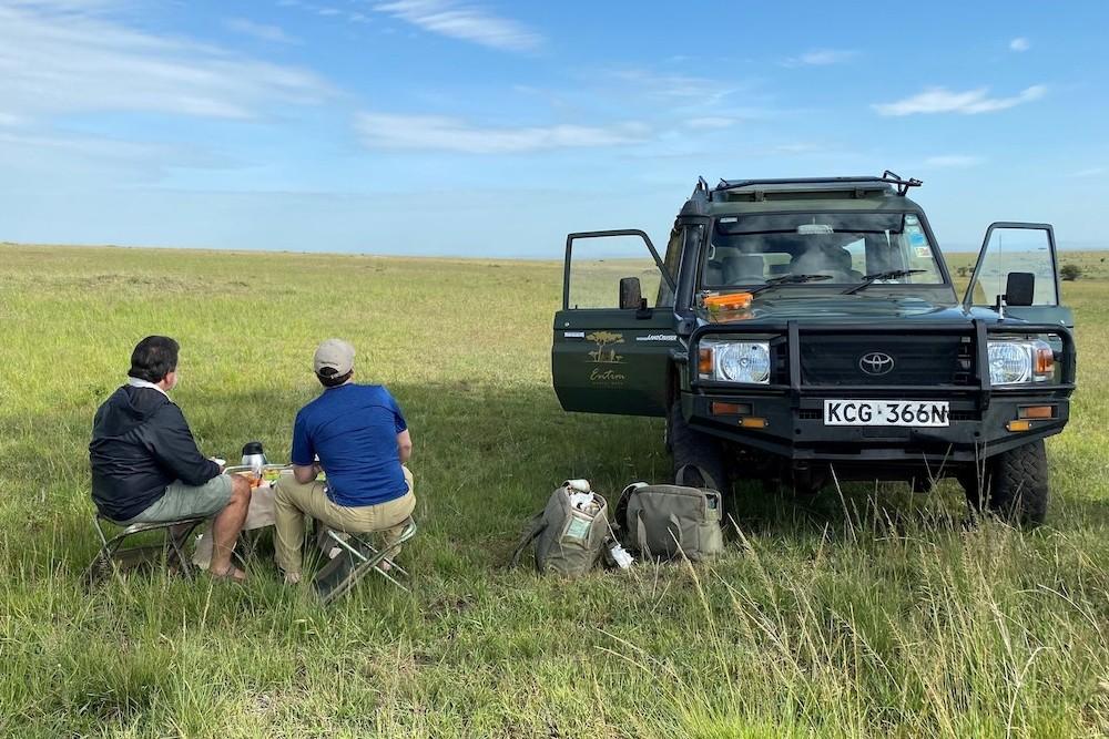 two travelers next to jeep in empty Kenya Mara plain