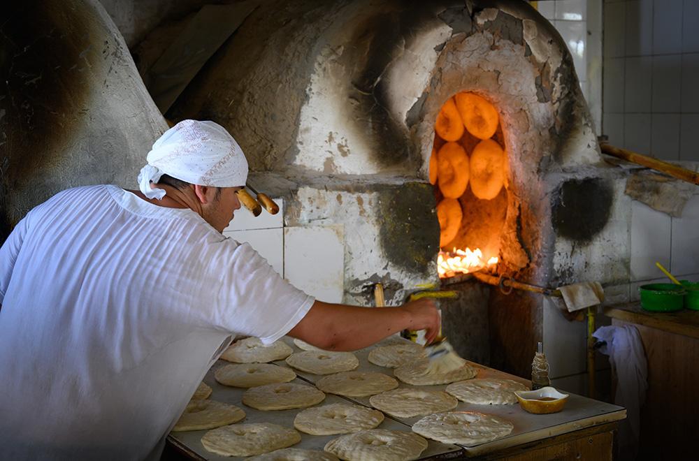 baker baking bread in oven in Uzbekistan