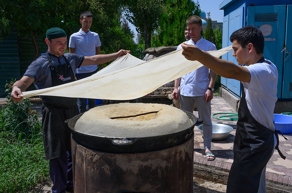 Uzbekistan Men cook a truck tire sized pan of plov over a fire pit