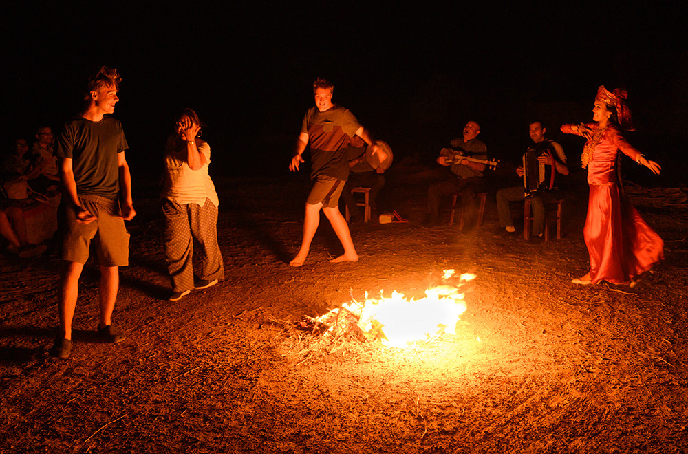 tourists and locals dancing around a campfire at a yurt camp in Uzbekistan