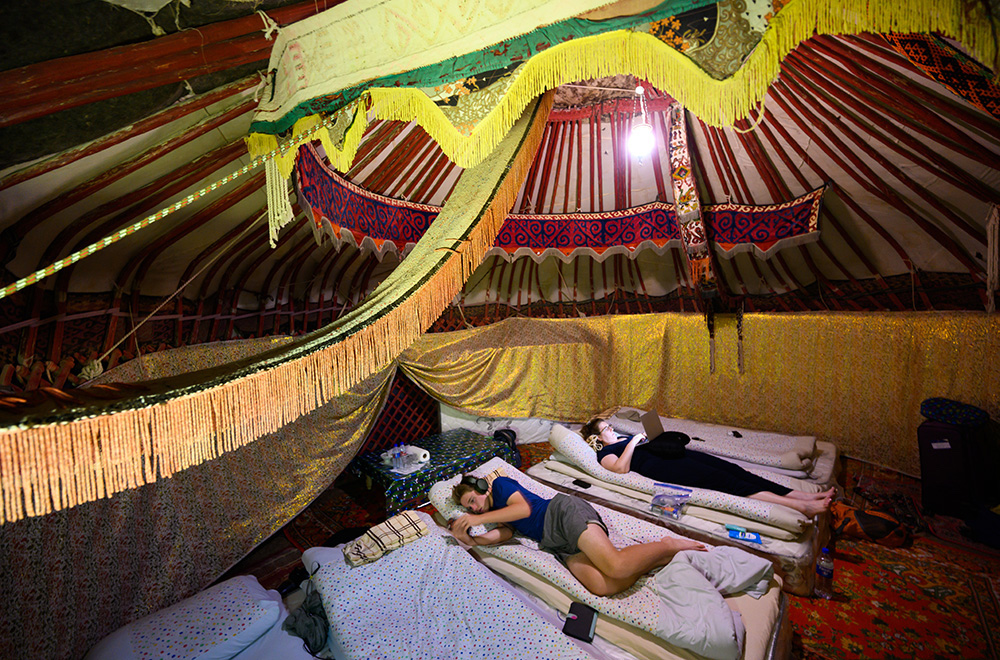 two teenage tourist boys resting inside a yurt at a yurt camp in Uzbekistan