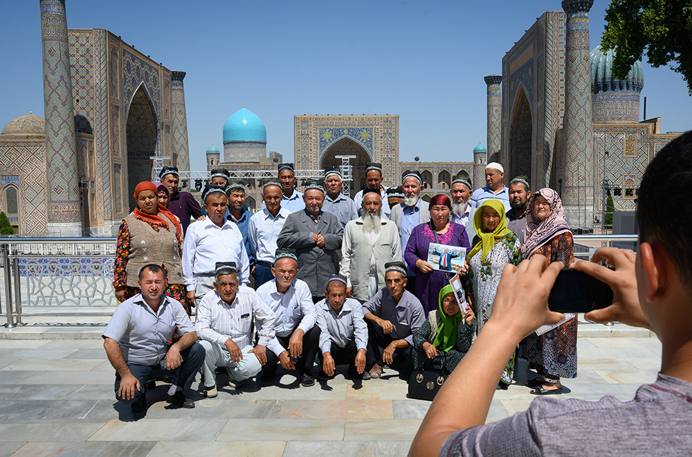 Local Uzbek tourists pose in front of the Registan in Samarkand Uzbekistan