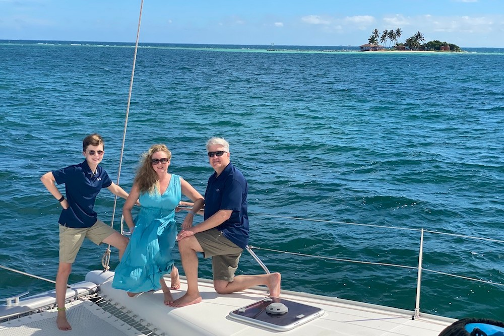 family posing on a private yacht on the ocean in Belize