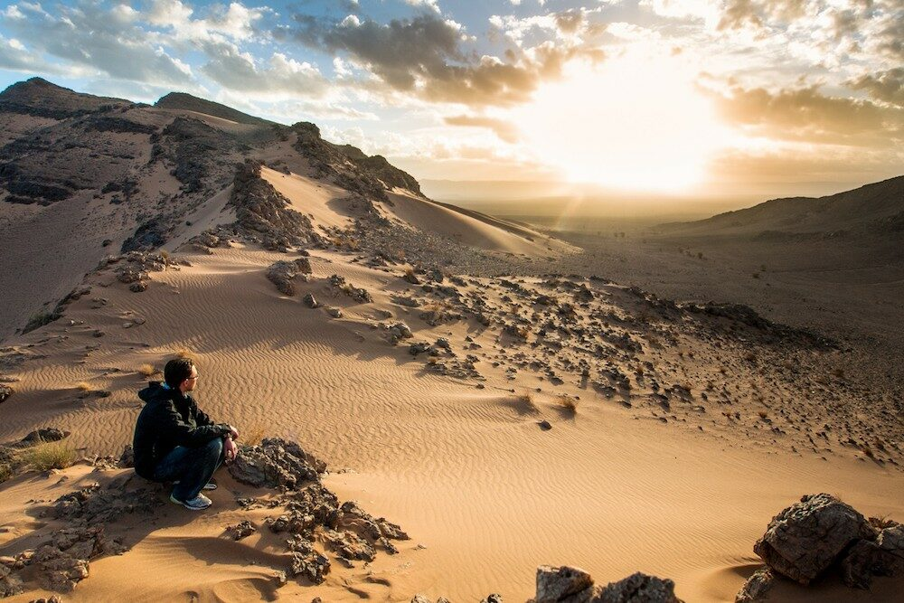 A man crouching and Watching the sunrise in the sahara desert Morocco