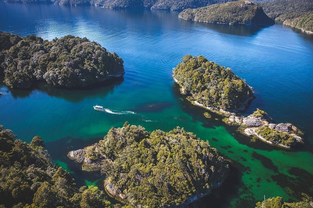 aerial view of boat in blue waters of Dusky Sound New Zealand
