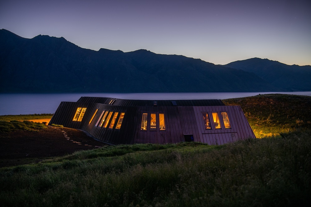 hotel cottage lit from inside in the dusk of New Zealand