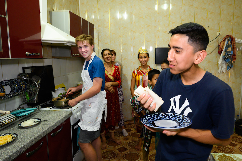 Uzbekistan - tourist boy cooking for local family in their home