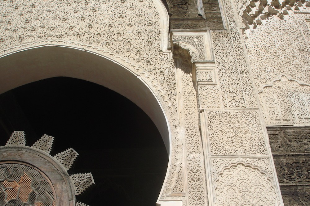 white lacy architecture at the Ben Youssef Madrasa in Morocco