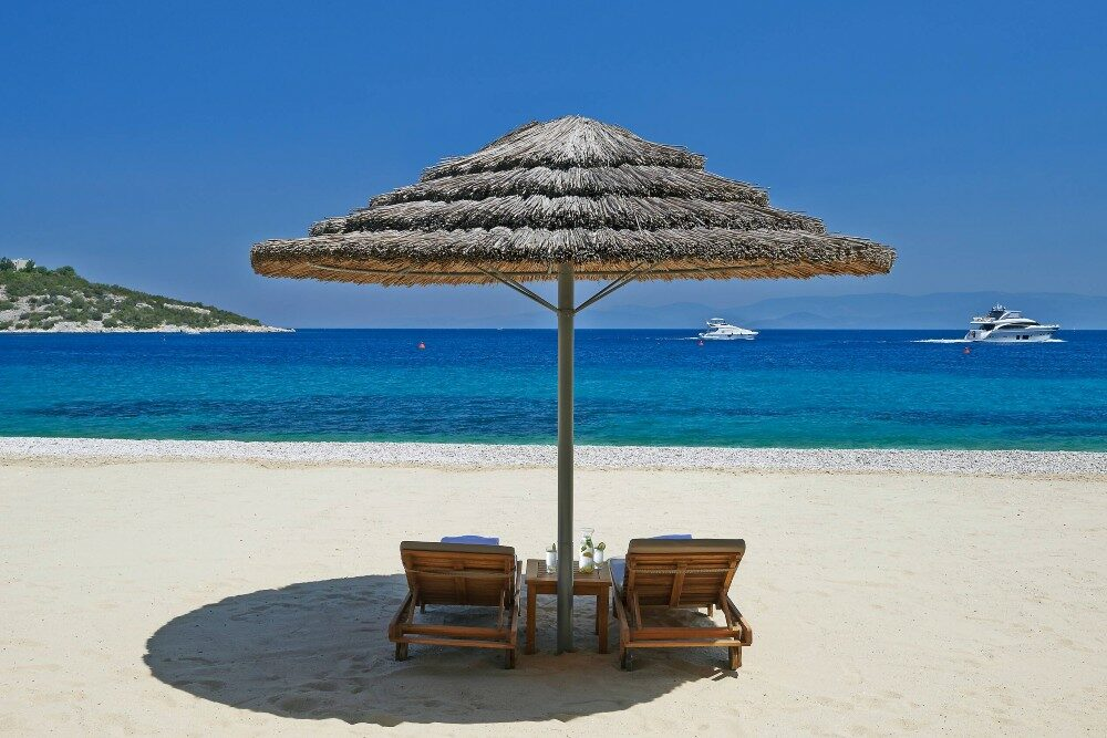 beach lounges under a palapa on the beach looking out to the blue ocean with boats in the water at the Mandarin Oriental hotel Bodrum Turkey