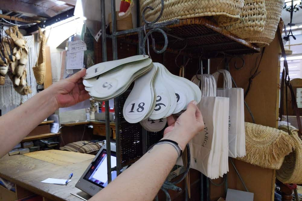 queue ticket numbers in shape of shoes at La Manual Alpargatera, oldest espadrilles shop in Barcelona